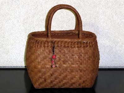 ヤマブドウのかごバッグに木彫りのチャームをつけた。