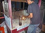 ココナッツの殻に油をかけて火をおこす