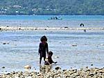 潮干狩りをする子供と観光客のボート