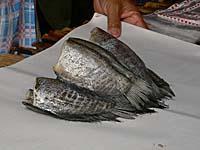 川でとれたと思われる魚を包んでいるところ。