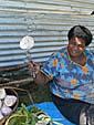 芋をナイフでぶっさしてポーズをとるおばちゃん