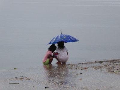 港で雨の中たたずむ少女たち。止まないかなぁ?