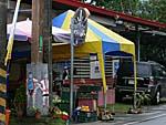 野菜を売るテントの横に原住民族が彫られた柱