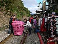 線路上で天灯を揚げる観光客