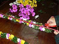 花の冠の仕上げ。余計な茎をはさみで切っているところ