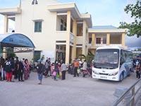 港の事務所に横付けされたバスと人々